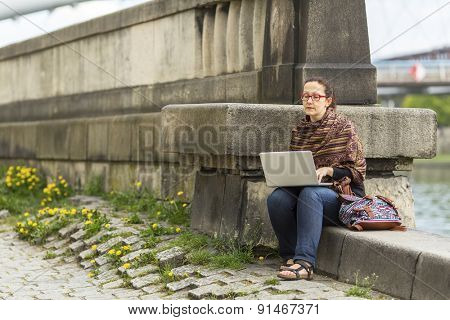 Young woman working on laptop while sitting on a stone embankment. Freelance.