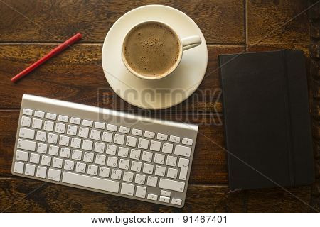 Computer keyboard, Cup of coffee, a notebook and red pencil on the table made of old dark wood.