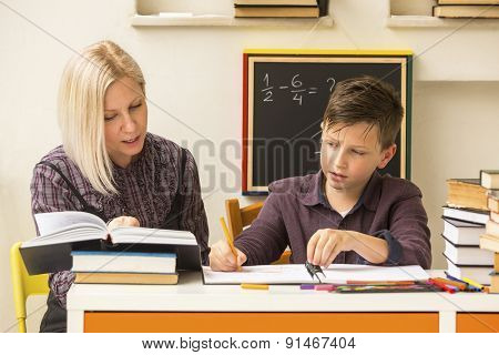 Schoolboy do homework at home with a tutor.