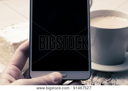 Hand Holds Mobile Phone In Front Of Coffee Cup