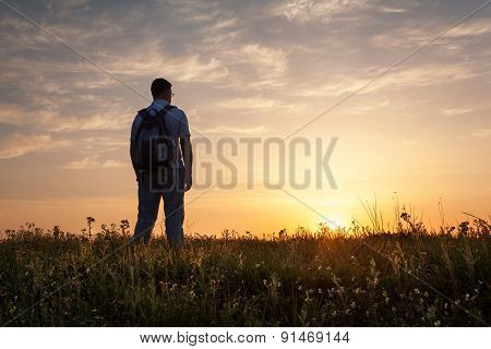 Silhouette of man with arms raised up and beautiful sky. Element of design. Summer sunset