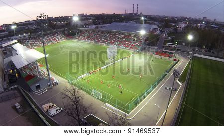 MOSCOW, RUSSIA - APR 28, 2014: Aerial view of football teams play on field with illumination near Locomotive Small Sports Arena.