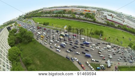 RUSSIA, MOSCOW - MAY 14, 2014: Many cars ride on Volgogradsky avenue by highway near Renault auto show and Avtoframos company. Panorama