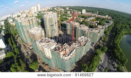RUSSIA, MOSCOW - MAY 23, 2014: City panorama with construction site of residential complex Vinogradny on lake shore at spring sunny day. Aerial view