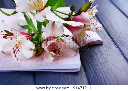 Beautiful alstroemeria with napkin on wooden background