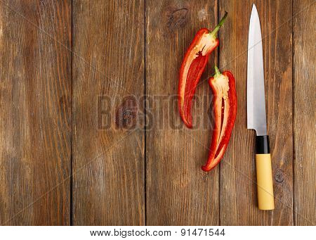 Halves of pepper chili with knife on wooden background