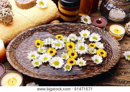 Beautiful spa composition with candles and flowers on table close up