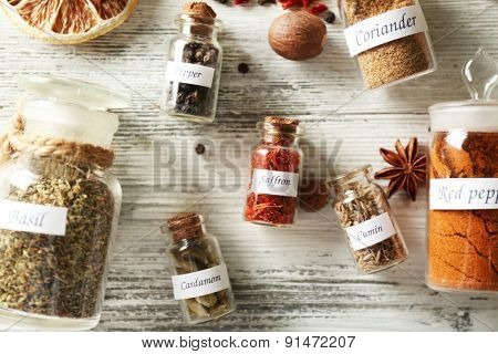 Assortment of spices in glass bottles on wooden background