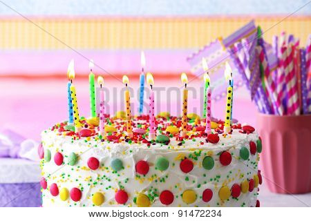 Birthday cake with candle on colorful striped background