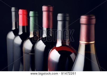 Wine bottles in row on black background
