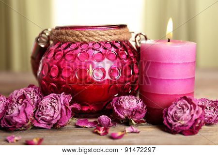 Spa still life with candle and dried roses on wooden table, closeup