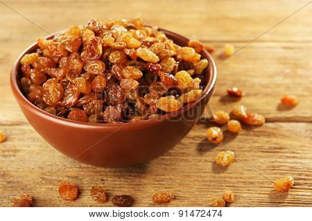Raisins in bowl on wooden table, closeup
