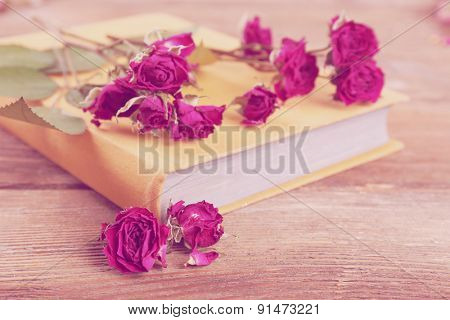 Dried roses with book on wooden table, closeup