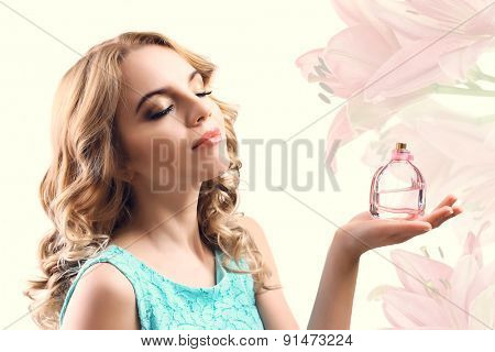 Beautiful woman with perfume bottle on light background
