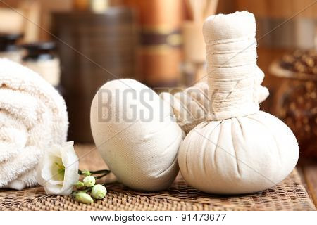 Beautiful spa composition with massage bags on table close up