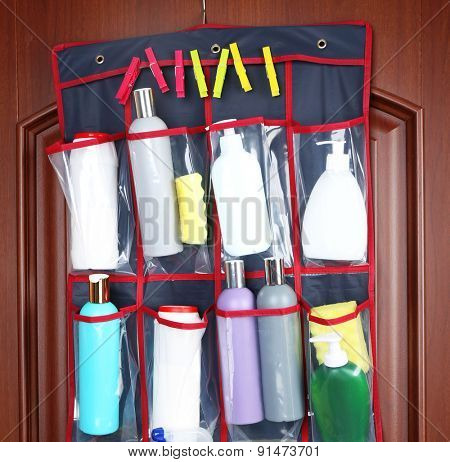 Different detergents in hanging bag wooden door