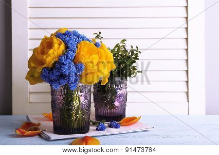 Composition with fresh spring flowers in glass vases on wooden background