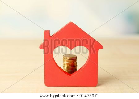 Model of house with coins on bright background