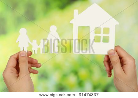 Female hands holding paper house and family on green blurred background
