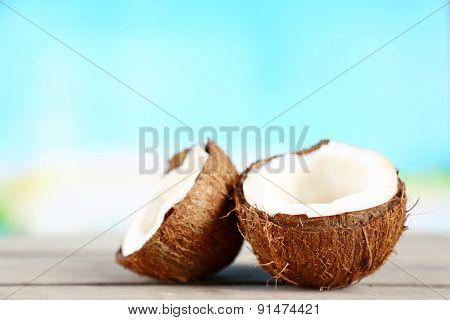 Coconut on wooden table on bright blurred background
