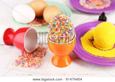 Decoration Easter eggs with colorful beads on wooden table, closeup