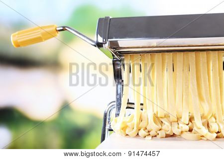 Making noodles with pasta machine on bright blurred background