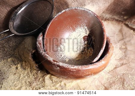 Flour with utensil on burlap cloth, closeup