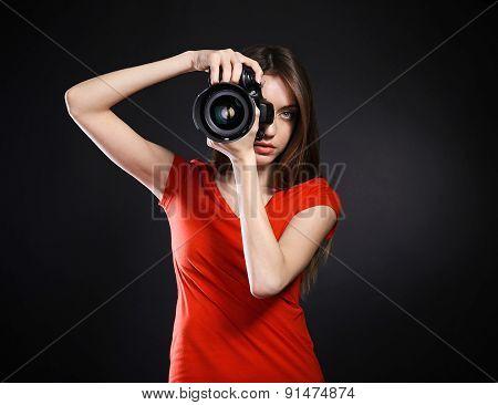 Young female photographer taking photos on black background