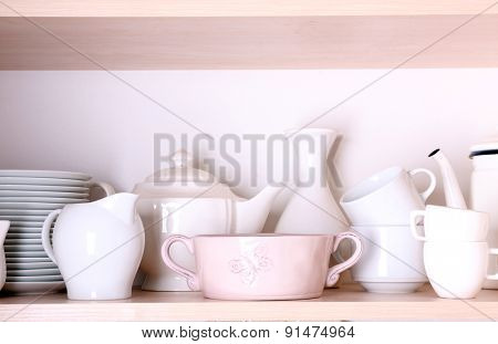Kitchen utensils and tableware on shelf