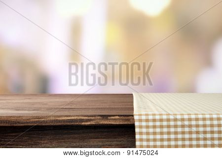 Empty wooden table with napkin and light background