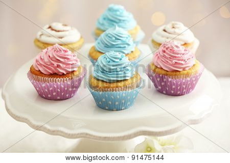 Delicious cupcakes on cake stand on table on light background