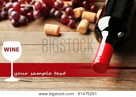 Bottle of wine with corks and grapes on wooden table background