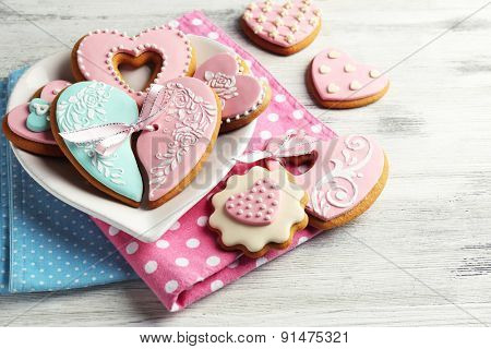 Heart shaped cookies for valentines day on plate, on color wooden background
