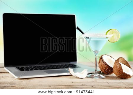 Laptop and glass of summer cocktail on wooden table, on bright blurred background