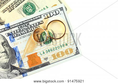 Golden wedding rings on banknotes, isolated on white. Marriage of convenience