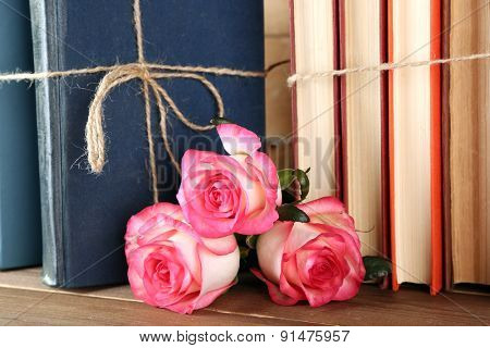 Tied books with pink roses on wooden table, closeup
