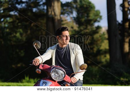 Handsome brunet young man in casual clothing near red scooter