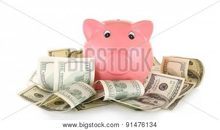 Piggy bank on pile of dollars isolated on white