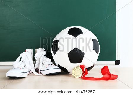 Sport shoes, soccer ball and golden medal on blackboard background