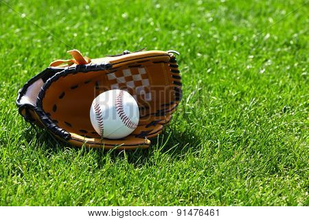Baseball ball and glove on green field