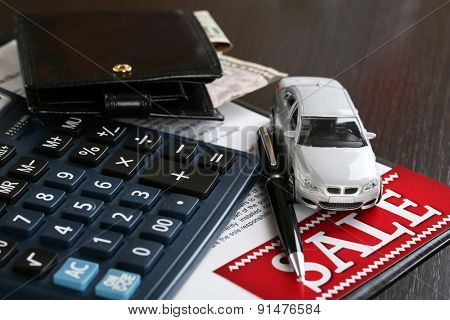 Tablet, calculator and toy car on table close-up