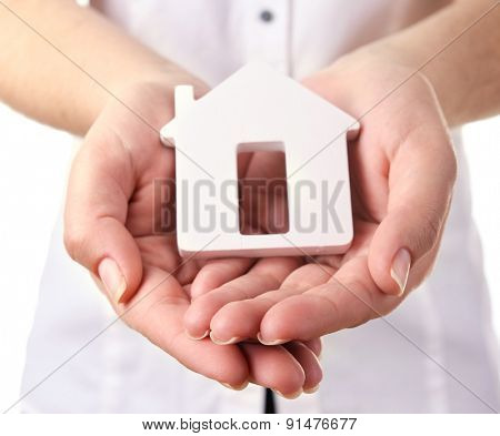 Female hands with small model of house, closeup