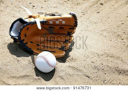 Baseball ball and glove on sand