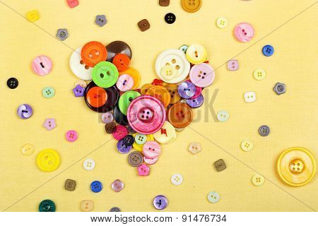 Sewing buttons heart on cloth background