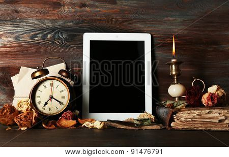 Ancient things and tablet on wooden background