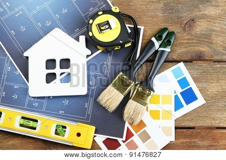 Color samples, decorative house, gloves and paintbrushes on wooden table background
