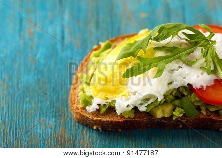 Tasty sandwich with egg, avocado and vegetables on wooden background