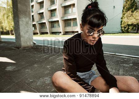 black haired tattooed lady sitting on longboard in backyard