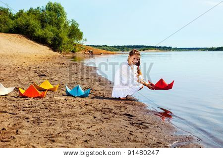 Smiling girl launches paper boat in lake