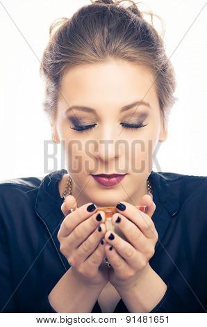 Young woman smelling hot coffee
